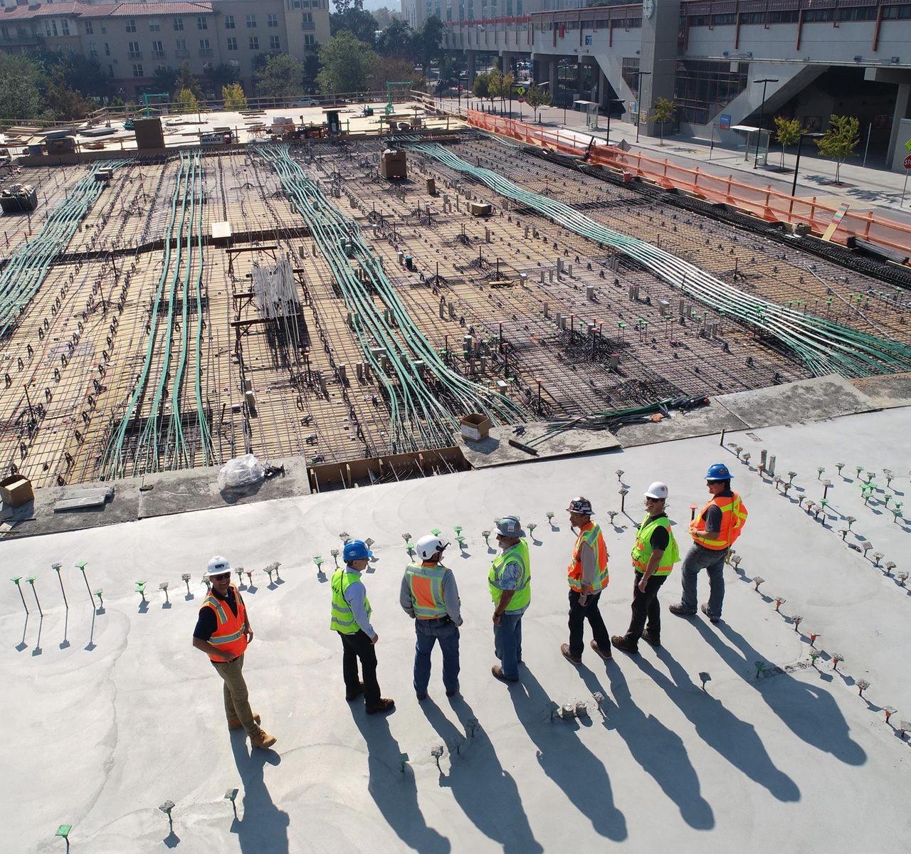 Des ouvriers sur le toit d'un chantier survolé par un drone