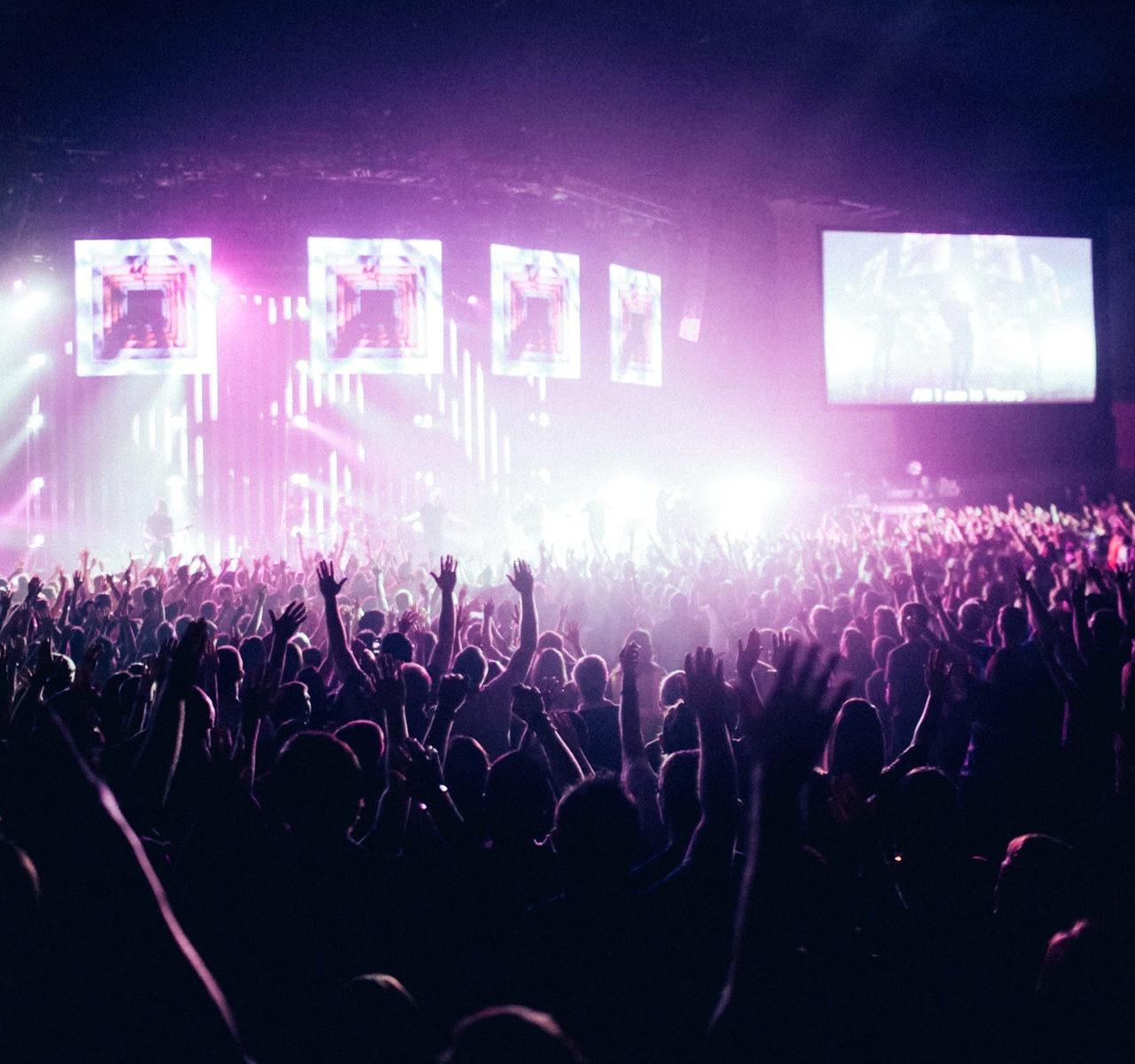 Un salle de concert avec un groupe de musique sur scène pendant un festival