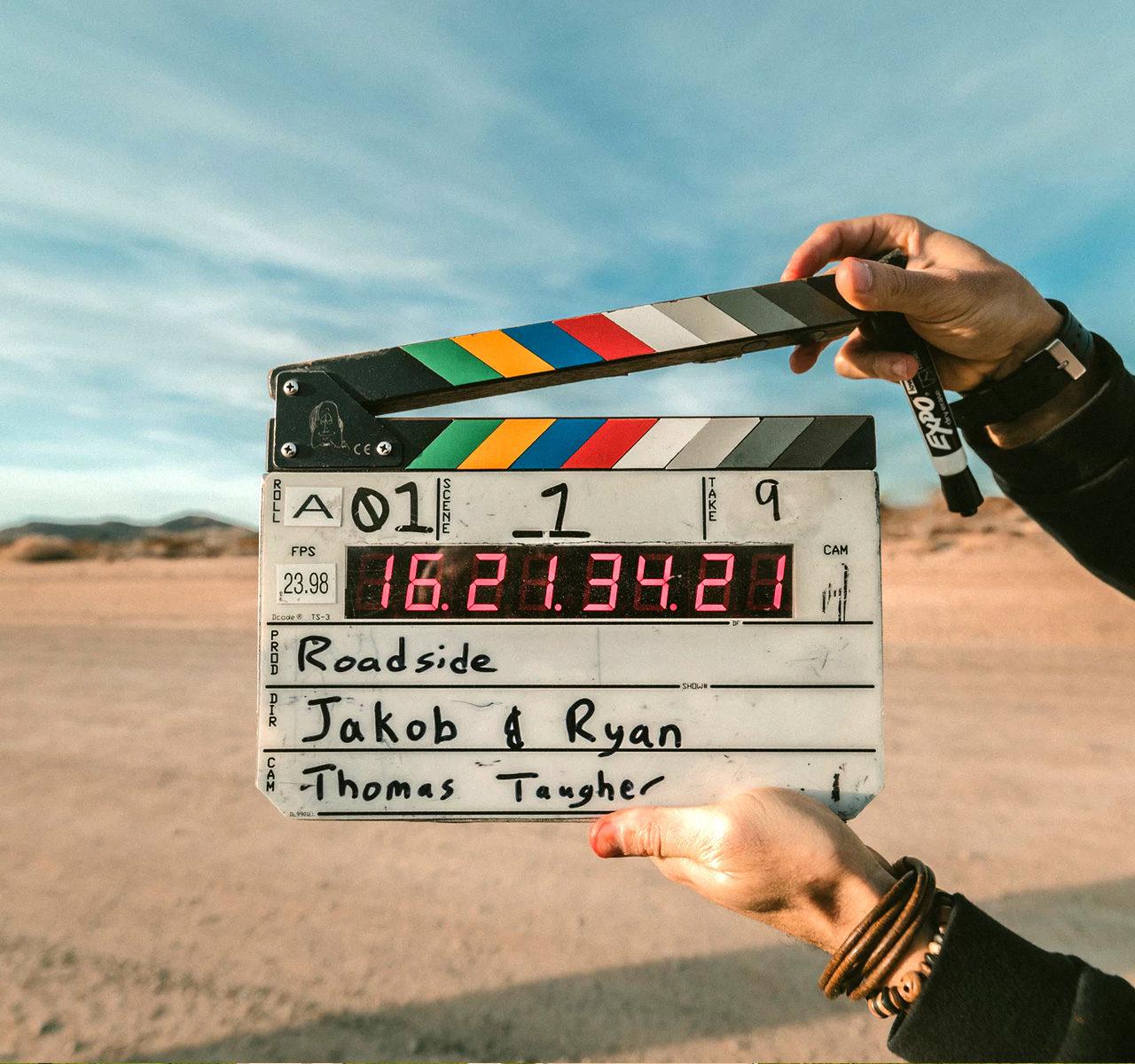 Un homme tient un clap de tournage de film